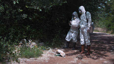 Two biologists in protective suits exploring ground and plants in woods. Inspect existence of garbage in the nature Stock Photo