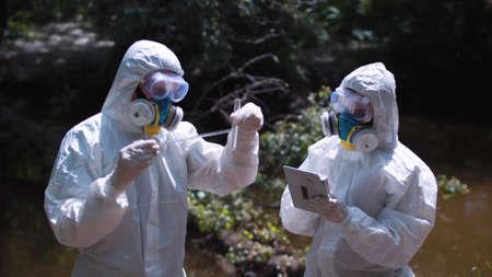 contaminacion del agua: Dos hombres en trajes de riesgo biológico y máscaras de muestreo de agua de un arroyo o un río pipetear una muestra en un tubo de ensayo para el análisis químico de los contaminantes.