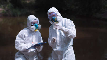 Two people wearing white environmental suits testing water in nature.