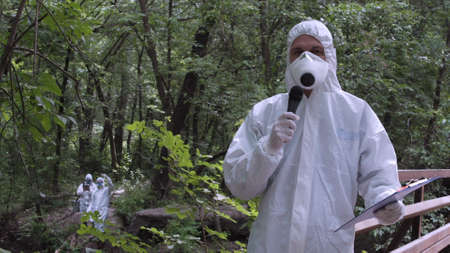 ecologist: Man wearing protective suit holding file in hands and speaking microphone while looking at camera on nature. Stock Photo
