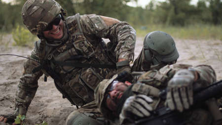 The Commander takes away from under firing of the soldier in the field of fight