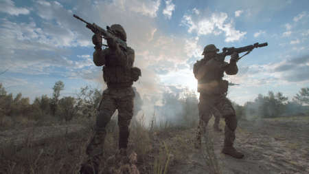 Silhouettes of soldiers walking on battlefield and aiming with guns.