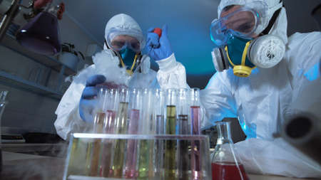 Two scientists in full biohazard masks with breathing apparatus working together in a chemical laboratory with hazardous samples conducting tests in a low angle view across a rack of text tubes.