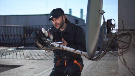 Ingénieur ou technicien vérifiant ou installant une antenne antenne parabolique et amplificateur sur le toit d'une grande hauteur urbaine à l'aide d'une tablette numérique Banque d'images