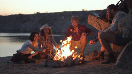 Group of multiracial people sitting around campfire grilling marshmallows and having fun on coast.