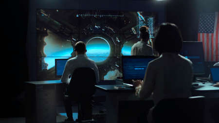 Back view of people working and managing flight in mission control center. Landing of spaceship on Moon.