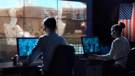 Vue arrière des personnes travaillant et gérant le vol dans le centre de contrôle de mission. Éléments de cette image fournis par la NASA. Banque d'images - 84492572
