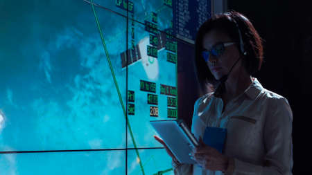 Side view of woman working at computer in space mission control center. Controlling the orbiting international space station ISS. Stock Photo