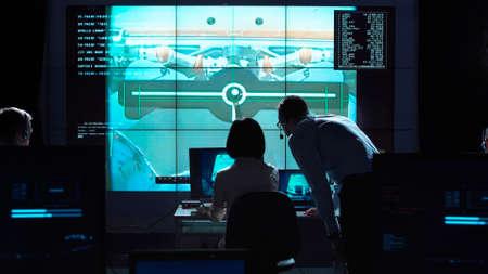 Achtermening van de mens en vrouw in ruimtevluchtcontrolecentrum. Docking van ruimtemodules.