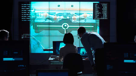 Back view of man and woman in space flight control center. Docking of space modules.