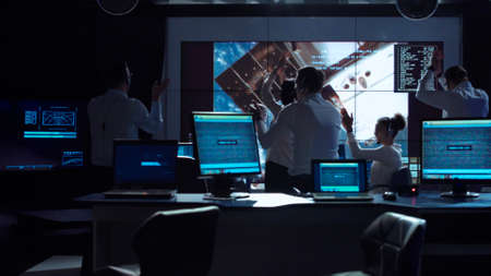 Group of supervisors celebrating docking of spaceship in dark room of mission control center.