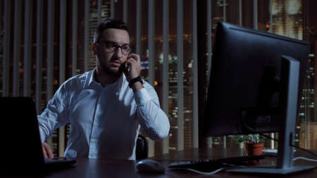 Man working in office at night sitting at laptop and communicating with phone. 免版税图像