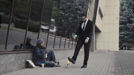 The businessman banishes the bearded homeless man and throws back his cup with coins.