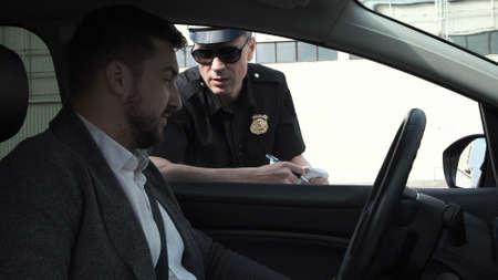 Policía detiene a un conductor en un automóvil para interrogarlo a través de la ventana en una ofensa de tráfico Foto de archivo