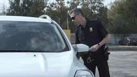 警察官が車両の運転手を止めて、車の開いた窓から疑惑について尋問する 写真素材