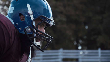 Side view close-up of the head of a determined American football player wearing protective blue helmet during match Stock Photo