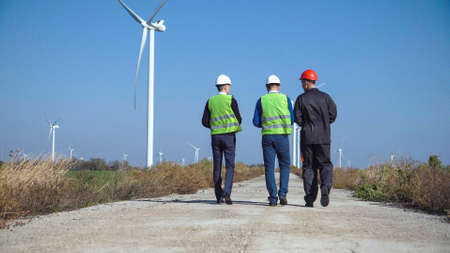 Three engineers wearing hard hats walking along road at wind farm on sunny day view from back Stock Photo