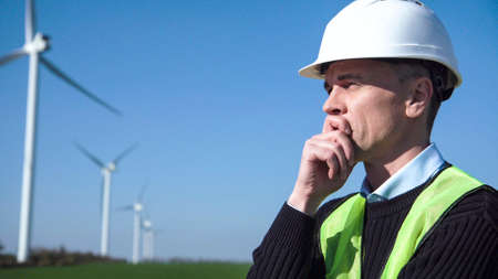 Thoughful engineer with hard hat standing against wind turbine on sunny day Stock Photo