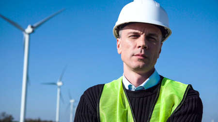Close shot of adult engineer in green vest and white hard hat with wind turbines on background looking at camera