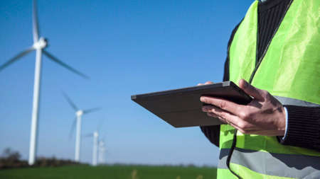 Close up view of engineer man hands working with digital tablet against wind turbine on sunny day
