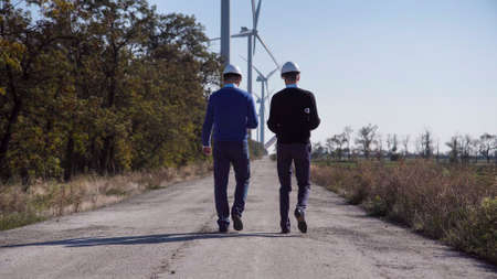 Rear view of engineers walking along road towards wind farm with turbines on sunny day Reklamní fotografie