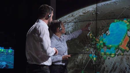 Grupo de dos científicos que observan y rastrean huracanes en un mapa y analizan el clima. Elementos de esta imagen proporcionada por la NASA.