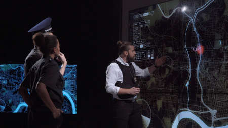Coworking policemen watching GPS data on electronic map while spying bandit team and officers discuss response tactics in front of large live screens in a futuristic office.