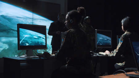 Single male bearded soldier in camouflage army uniform reviewing monitor of missle launch on large computer screen display Stok Fotoğraf - 89932213
