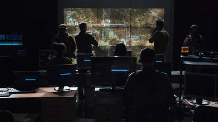 Group of soldiers or spies in dark room with large monitors and advanced satellite communication technology launching a missle. Includes flashing yellow light.