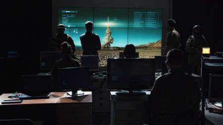 Gezaghebbende man die opdracht geeft om kernbom te lanceren en deze op digitaal scherm te volgen. Stockfoto - 92370289