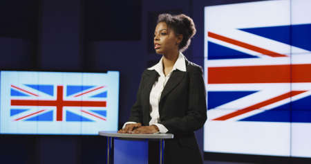 Formal African-American woman as official representative of Great Britain holding speech on press conference against screen with country flag.