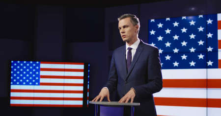 Public speaker or presenter in front of American flag standing at a small rostrum speaking and gesturing emphatically with his hands. Stock Photo