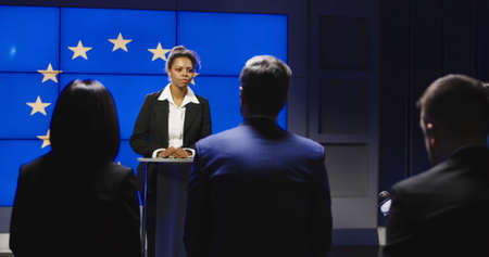 Serious African-American representative of European Union answering questions of journalists on news conference in semilit studio with EU flag on screen.