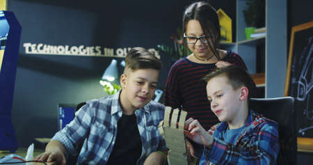 Group of content children creating carton prosthesis of arm with help of robotics. Stock Photo