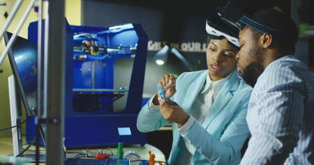 Group of black coworkers in laboratory wearing VR goggles and exploring 3d printing model and check quality of printed product. 스톡 콘텐츠