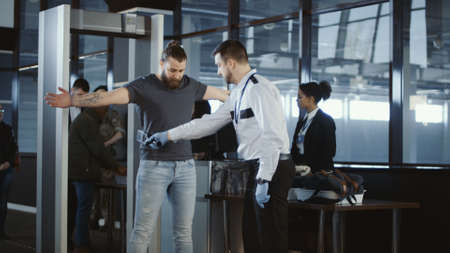 Security agent at an airport check-in gate patting down a bearded casual male passenger with outstretched arms after he passes through the metal detector scanner in the departures hall.