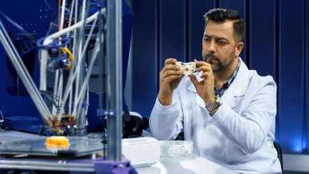 Serious man in laboratory exploring three-dimensional cranium fragment working for engineering medicine. Banco de Imagens