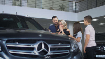 ZAPOROZHYE, UKRAINE - APRIL 3, 2018: The successful husband made a gift to his wife and gave her a Mercedes Benz car, the woman is very emotional and surprised and they hug themselves together near the car.