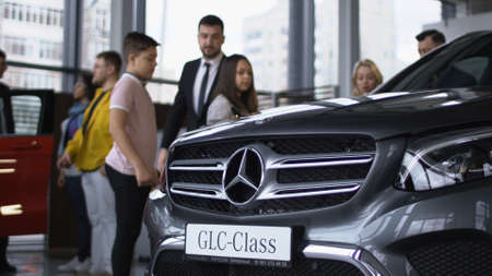 ZAPOROZHYE, UKRAINE - APRIL 3, 2018: View of expensive new car in auto salon with people and consultants walking around and having presentation.