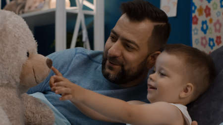 Cheerful man lying with adorable little boy in bed and playing with teddy bear before sleep