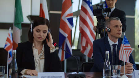 Formal international politicians in headphones sitting at table on summit and listening to speech translation in headphones Banque d'images