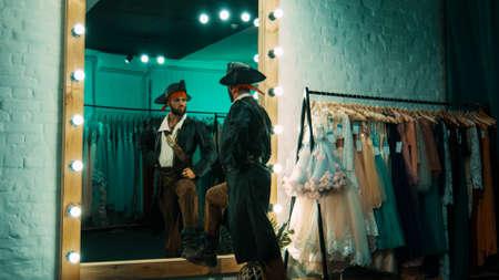 Vista posterior del hombre vestido con traje de pirata y de pie frente al espejo en el camerino practicando la escena de la actuación