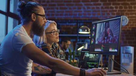 Jonge man en meisje in glazen die ideeën delen en aan videobewerking op computer werken die montage en kleurcorrectie doen