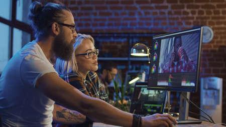 Młody mężczyzna i dziewczyna w okularach, dzieląc się pomysłami i pracując nad edycją wideo na komputerze, wykonując montaż i korekcję kolorów