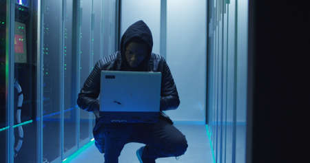 Medium shot of a hacker in a hoodie on laptop in corporate data center with rows of working rack servers