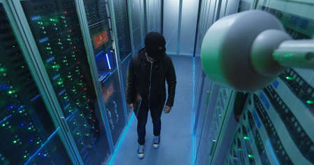 High angle shot of a masked hacker with his laptop waking through server rows then beginning attack
