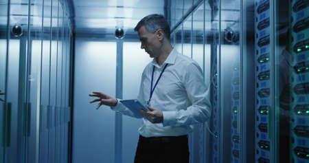 Plano medio de un técnico que trabaja en una tableta en un centro de datos lleno de servidores en rack que ejecutan diagnósticos y mantenimiento del sistema