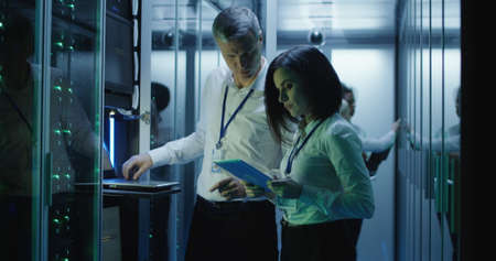 Side view of multiethnic man and woman with tablet diagnosing server hardware opening glass door of rack in data center corridor 스톡 콘텐츠