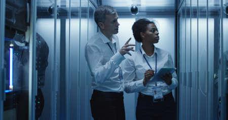 Diversos hombres y mujeres adultos que usan tableta y computadora portátil mientras diagnostican el hardware del servidor en un centro de datos moderno
