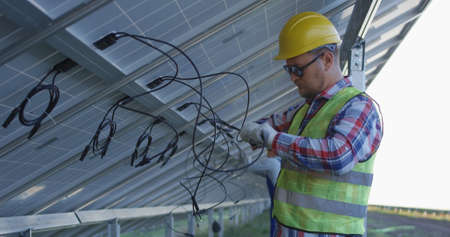 Medium shot of two electrical workers in hardhats connecting wires of solar panels at a solar farm